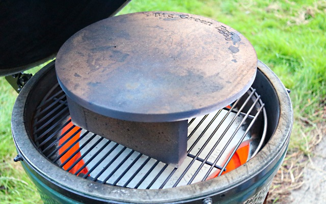 Big Green Egg set up to cook thin crust pizza. Fire bricks raise the stone.