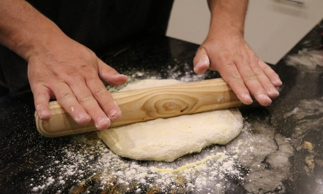 Rolling the dough on a surface with polenta and flour