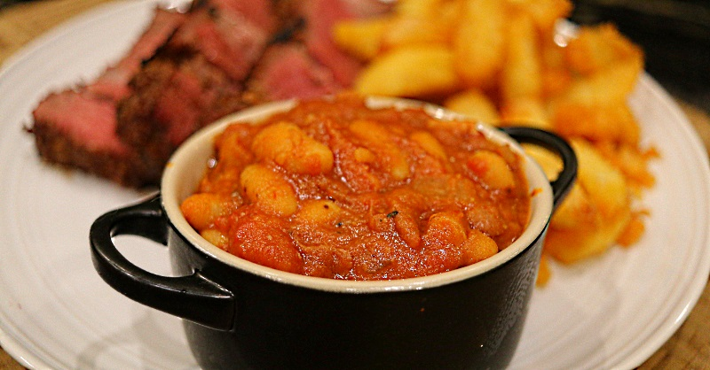 Smokey bourbon baked beans with ribeye steak and chips