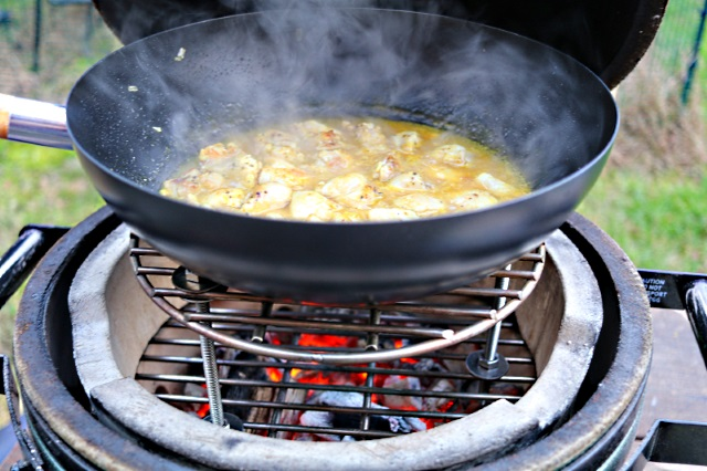 Vietnamese orange chicken with lemongrass simmering in a wok
