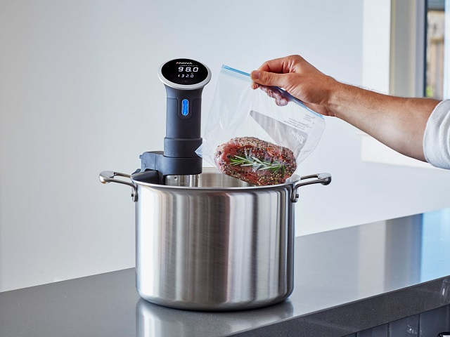 Anova sous vide device being used in a large kitchen pan