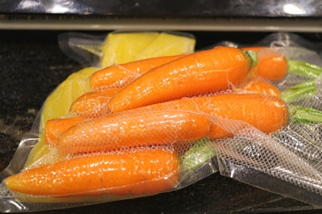 Carrots vacuum sealed with frozen cubes of orange juice