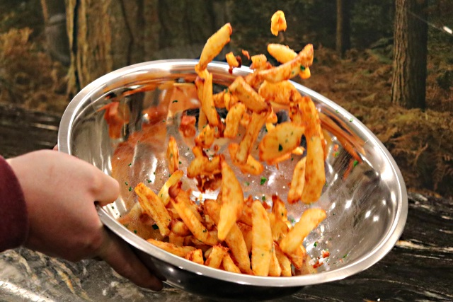 Tossing the chips in a salad bowl with oil and parsley