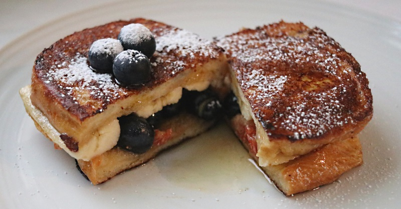 Banana and blueberry French toast dusted with icing sugar