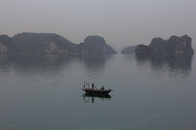 A fishing boat in the early morning mists of Halong Bay