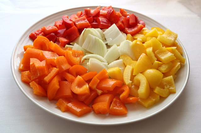 Red, yellow and orange peppers with onion ready for stir fry