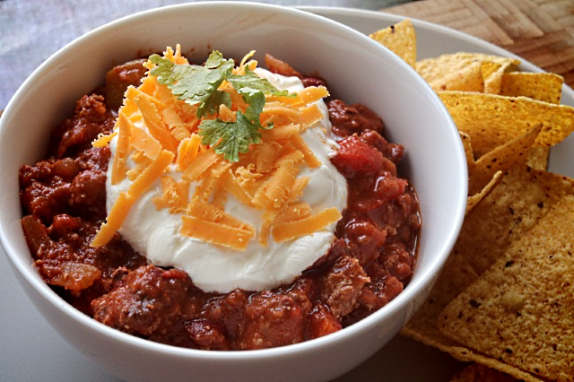 Over the top smoked chili with sour cream, cheese, coriander and tortilla chips
