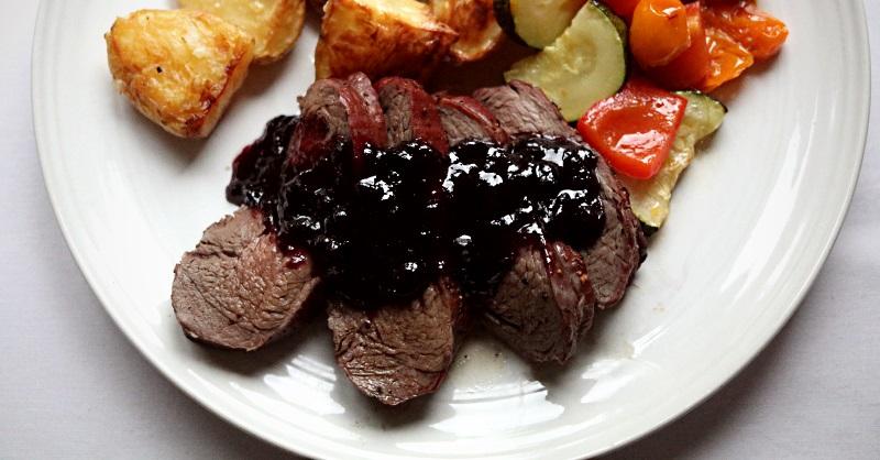 Roast venison haunch with huckleberry sauce