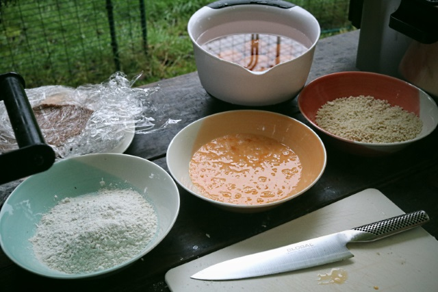 Three bowls with flour, beaten eggs and panko breadcrumbs