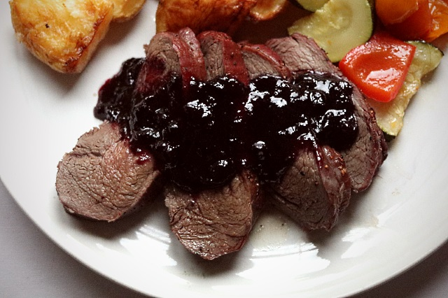 Roast venison haunch and huckleberry sauce served with vegetables