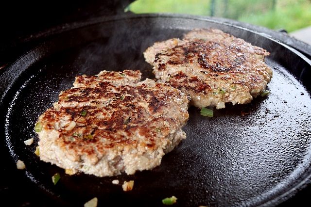Flattened burgers browning off on the cast iron surface