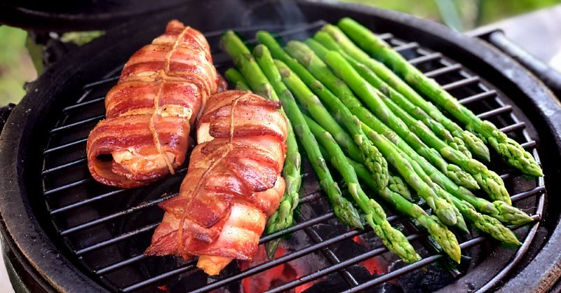 Bacon wrapped chicken breast searing with fresh asparagus