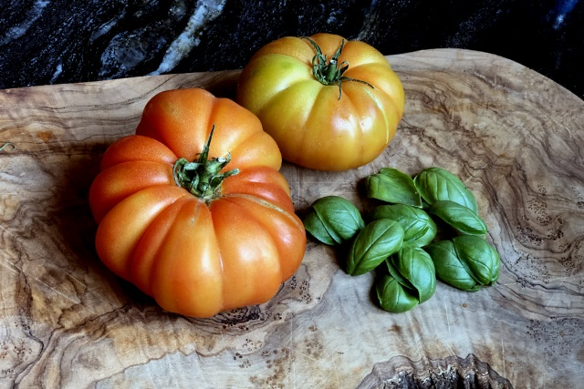 Buffalo heirloom tomatoes with fresh basil leaves
