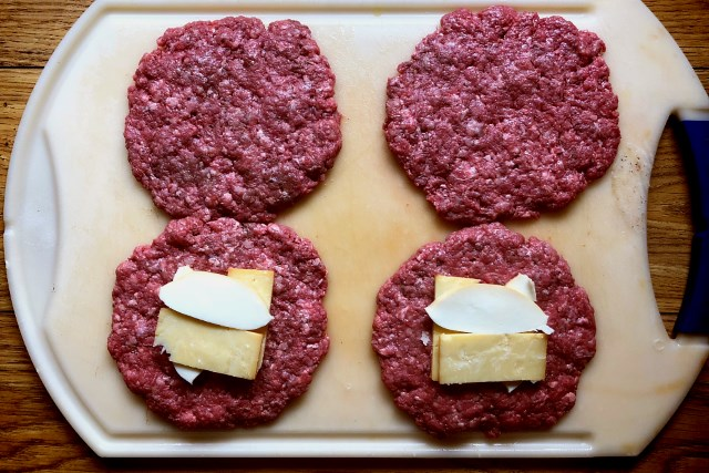 Four burger patties with cheese layered on two of them