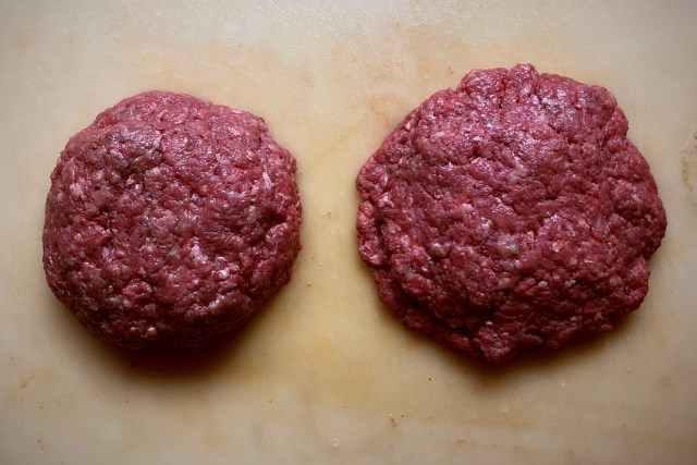 Two formed Jucy Lucy burgers, left hand one has been shaped