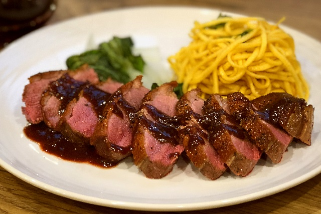 Duck breast with plum and tamarind sauce, noodles and pak choi