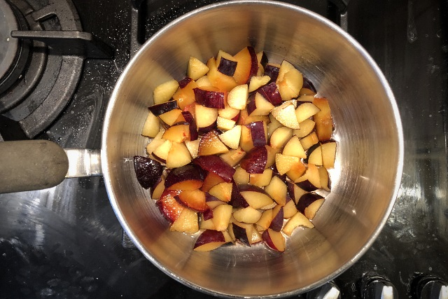 Plums steaming in a saucepan